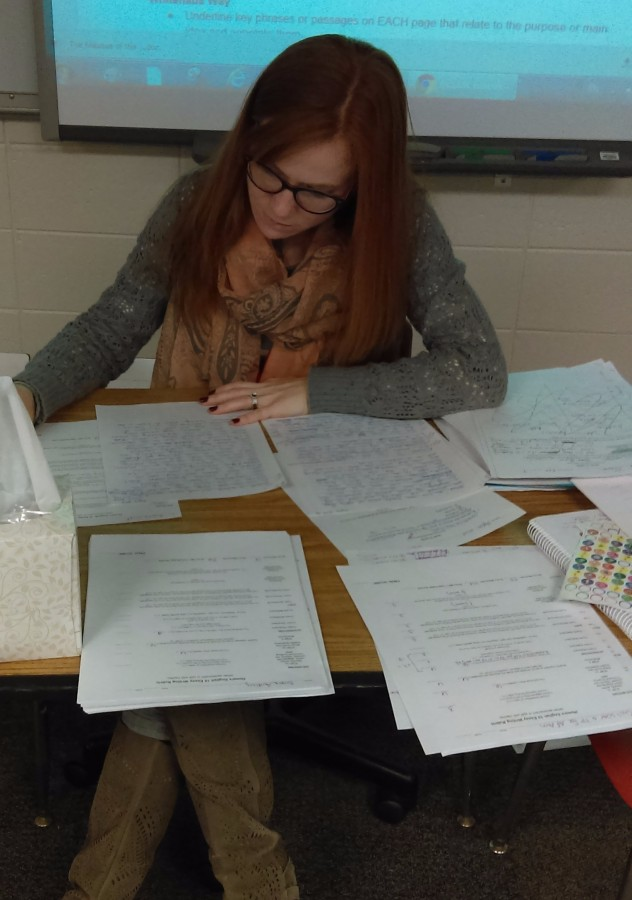 English teacher, Carol Whitehous, corrects papers in her classroom