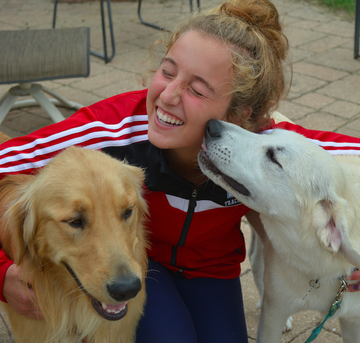 Sophomore Maria Turco poses for a picture with her dog and a fostered dog