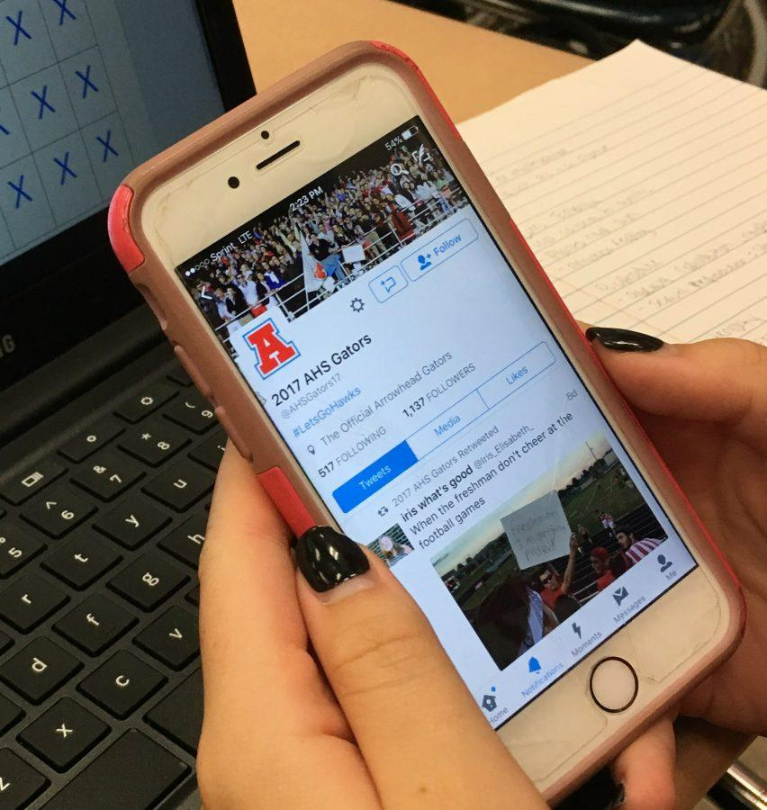 Student viewing the Arrowhead DECA Twitter page at school
