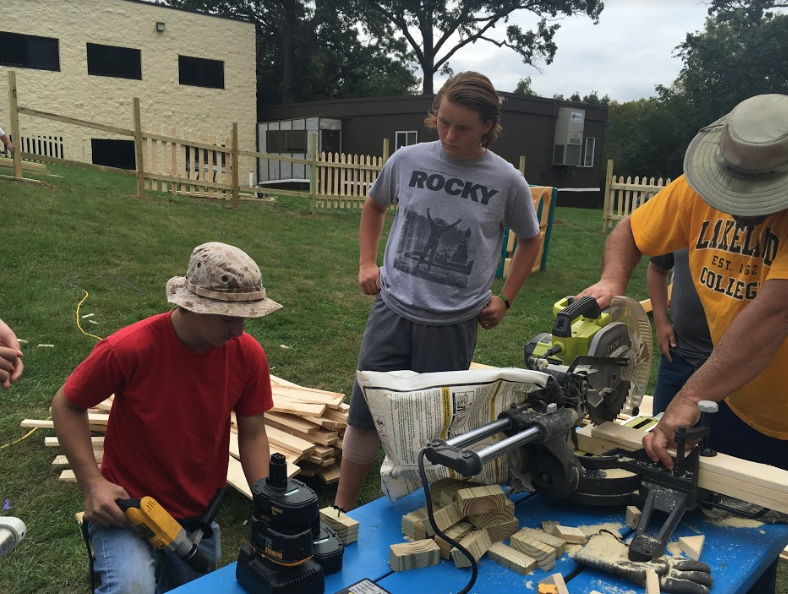 Derek Luetke (left) helps direct fellow scout, Dylan Niermeyer, how to properly drill.