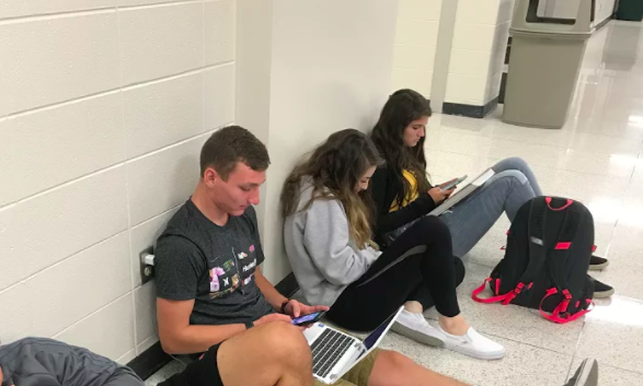 Students spending their free time in senior study hall to use their phones.