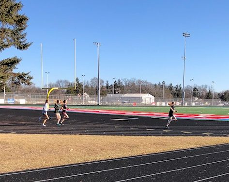 Girls track and field athletes run a warm up lap on the track before their sprints workout.